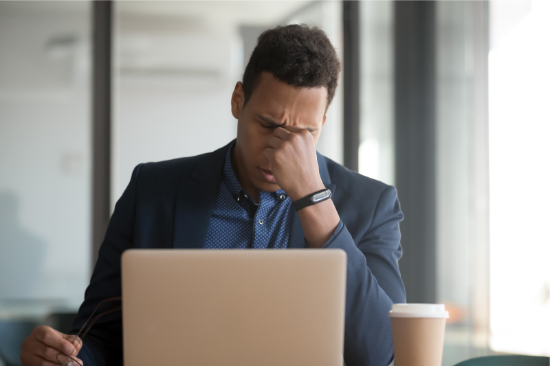 Black man upset while sitting in front of his computer