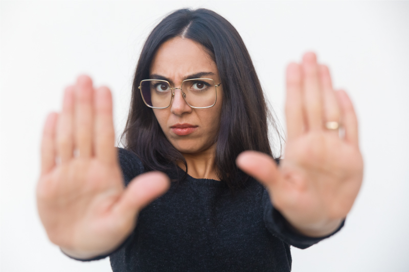women with hands saying stop